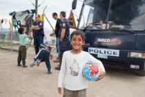 Kinder im Flüchtlingslager Idomeni, dahinter die Polizeibusse