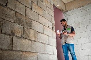 Omar an der Tür einer Flüchtlingswohnung.