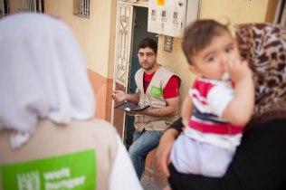 Mohammed (30) während er eine syrische Familie regsitriert.